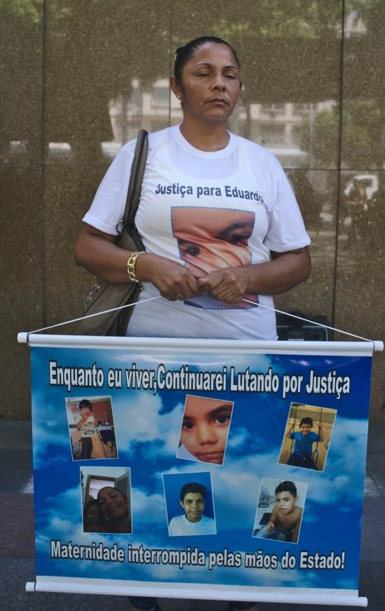 Terezinha de Jesus, mãe de Eduardo de Jesus, morto por PMs no Complexo do Alemão em 2015, segura cartaz com fotos de vítimas de Costa Barros. Foto: Leo Coelho
