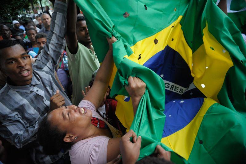 A bandeira do Brasil com buracos simulando balas foi levada também no enterro dos cinco jovens, em dezembro do ano passado. Foto: Fernando Frazão/Agência Brasil