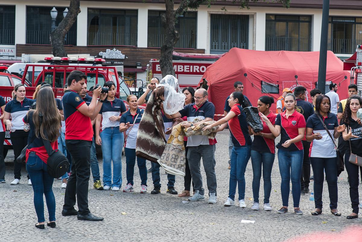 Voluntários da Igreja Universal fotografam a si mesmos enquanto doam aos desabrigados | Foto: Daniel Arroyo/Ponte